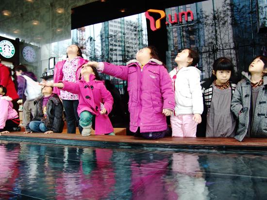 로비에 설치된 POND에 흥미를 보이고 있는 아이들